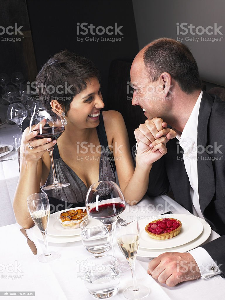 Couple sitting at dining table, holding hands, elevated view royalty-free stock photo