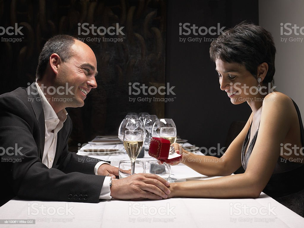 Couple sitting at restaurant, woman holding engagement ring, side view royalty-free stock photo