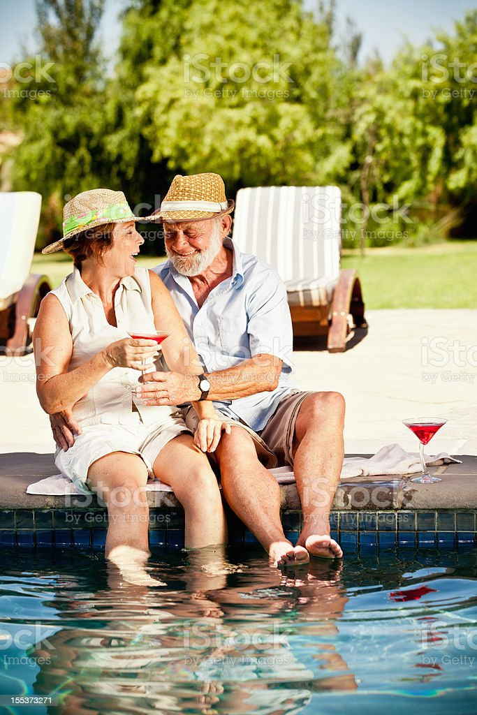 Couple Sitting at Swimming Pool with Cocktails royalty-free stock photo