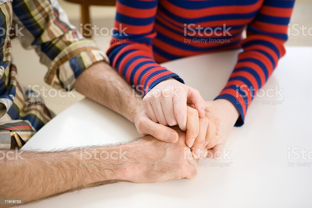 Couple sitting at table, holding hands royalty-free stock photo
