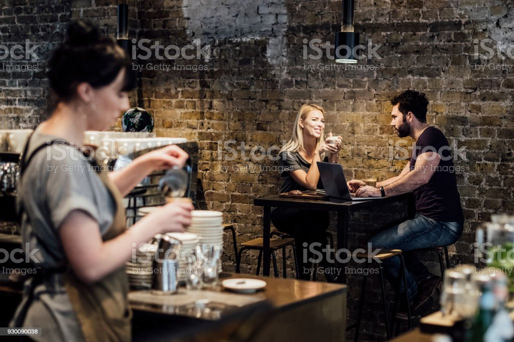 Couple sitting at table in modern cafe with waitress preparing drink in foreground stock photo