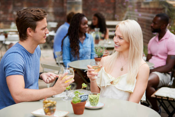 Couple Sitting At Table In Pub Garden Enjoying Drink Together stock photo