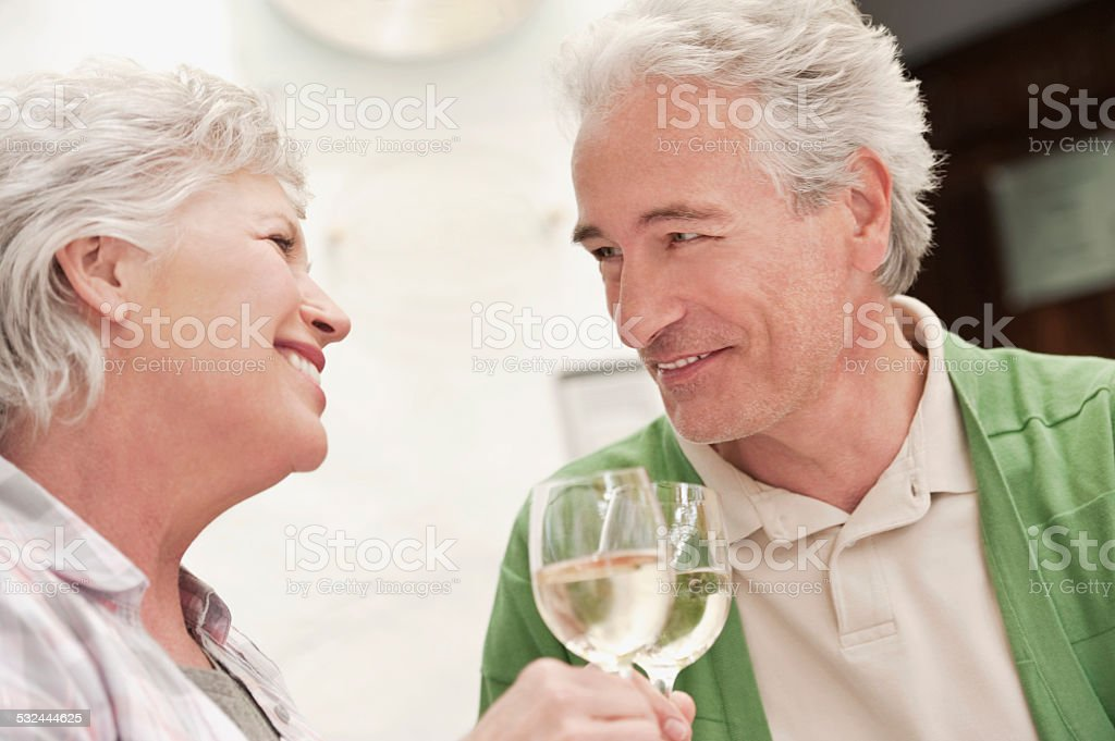 Couple sitting at table with wine glasses stock photo