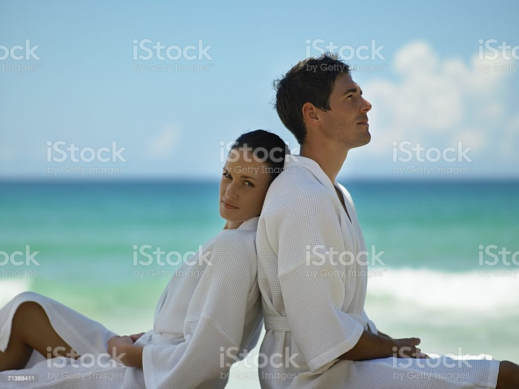 Couple sitting back to back on beach royalty-free stock photo