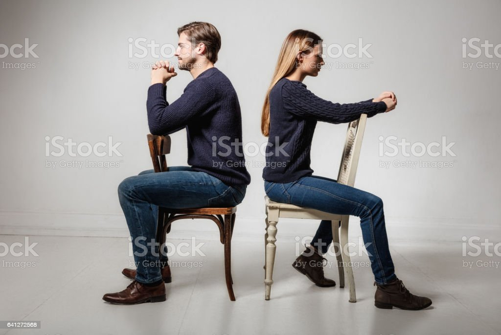 couple sitting back to back on chairs stock photo