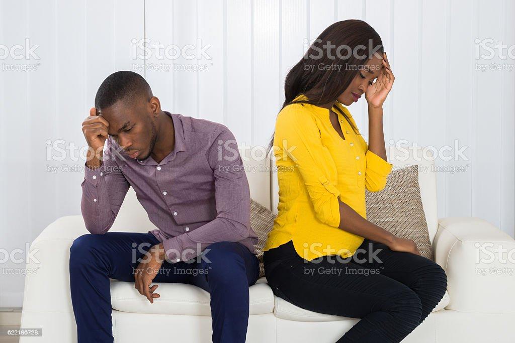 Couple Sitting Back To Back On Sofa stock photo