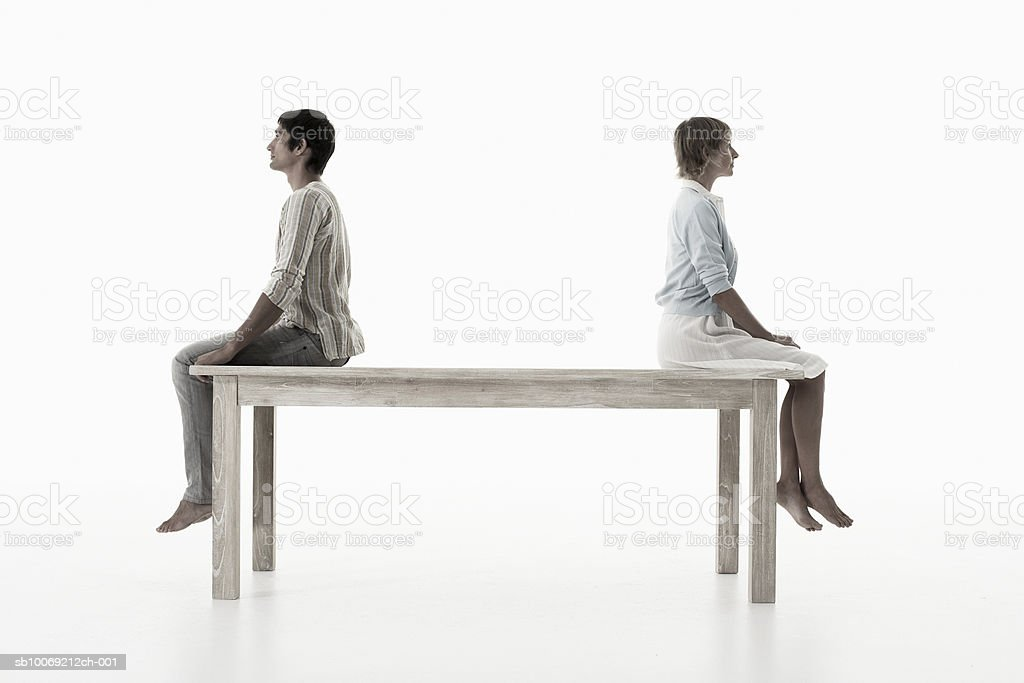 Couple sitting back to back on wooden table against white background, side view royalty-free stock photo