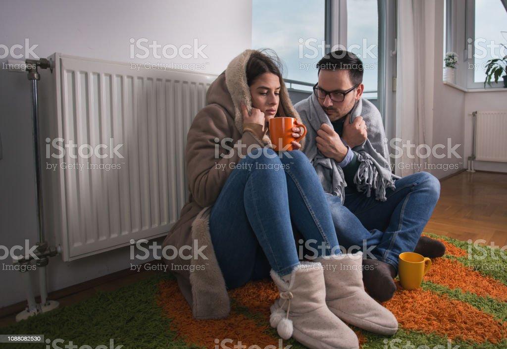 Paar sitzt neben Heizkörper – Foto