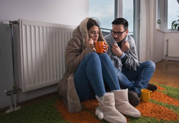 pareja sentada al lado del radiador - frío fotografías e imágenes de stock