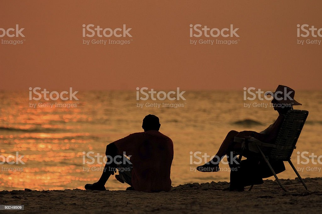 Couple sitting by beach royalty-free stock photo