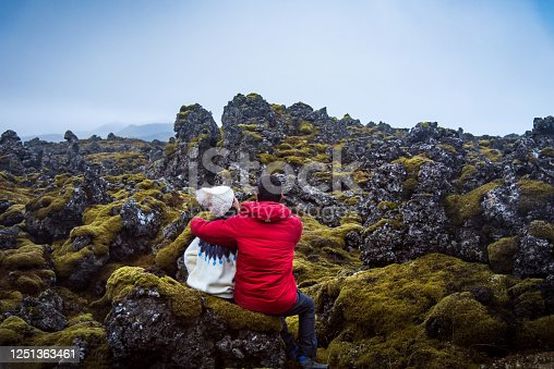 Happy couple sitting in a lava field in Iceland back view with copy space