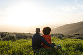 Couple sitting in a meadow and watching the sunset