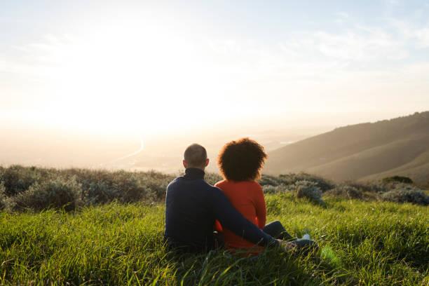 casal sentado num prado e assistindo o pôr do sol - escapismo - fotografias e filmes do acervo