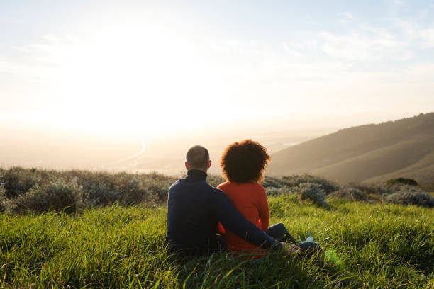 couple sitting in a meadow and watching the sunset - {{relatedsearchurl(carousel.phrase)}} foto e immagini stock