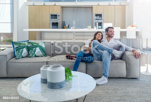 istock Couple sitting in a modern open plan house. 589448332