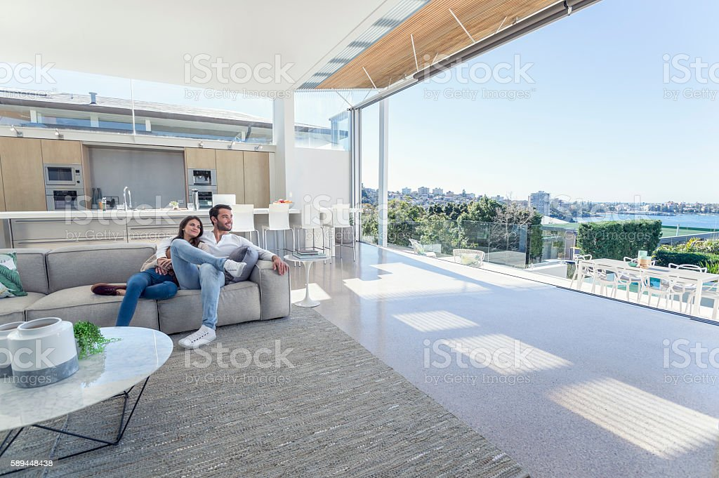 Couple sitting in a modern open plan house. - Photo