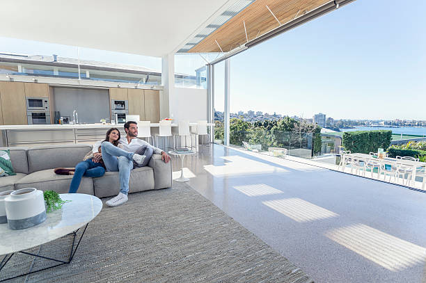 couple sitting in a modern open plan house. - modern lifestyle stock photos and pictures