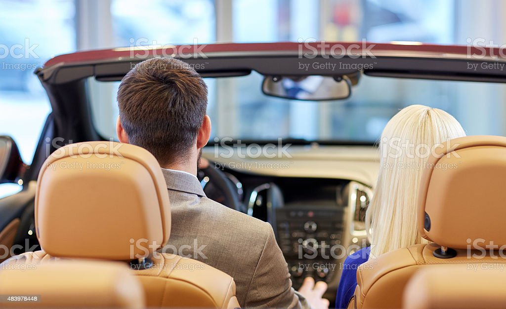 couple sitting in cabriolet car at auto show stock photo