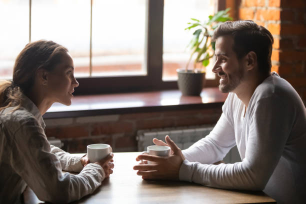 Couple sitting in cafe talking drinking tea or coffee Side view smiling biracial woman sitting at table in cafe with caucasian man couple talking in cozy coffeeshop drinking tea coffee. Heterosexual friends romantic relationships or speed dating concept individual event stock pictures, royalty-free photos & images
