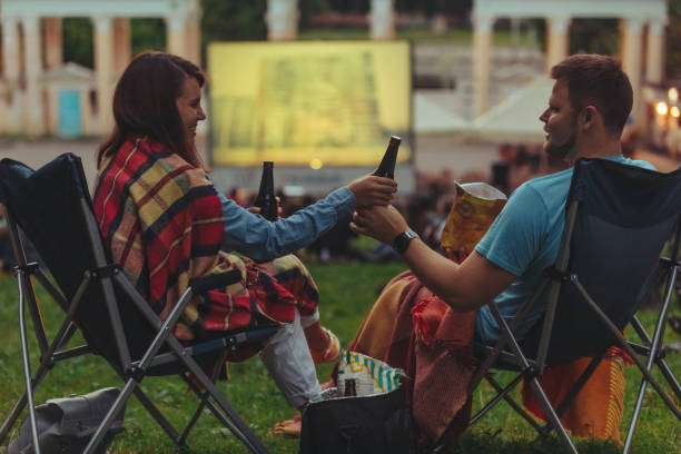 couple sitting in camp-chairs in city park looking movie outdoors at open air cinema stock photo