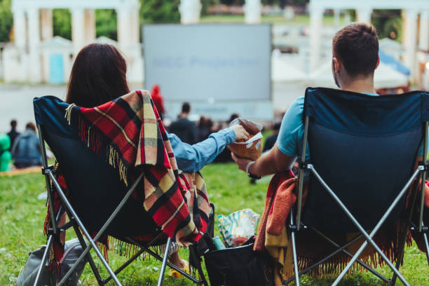 couple sitting in camp-chairs in city park looking movie outdoors at open air cinema - ambientazione esterna foto e immagini stock