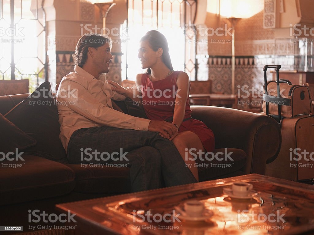 Couple sitting in exotic hotel lobby royaltyfri bildbanksbilder