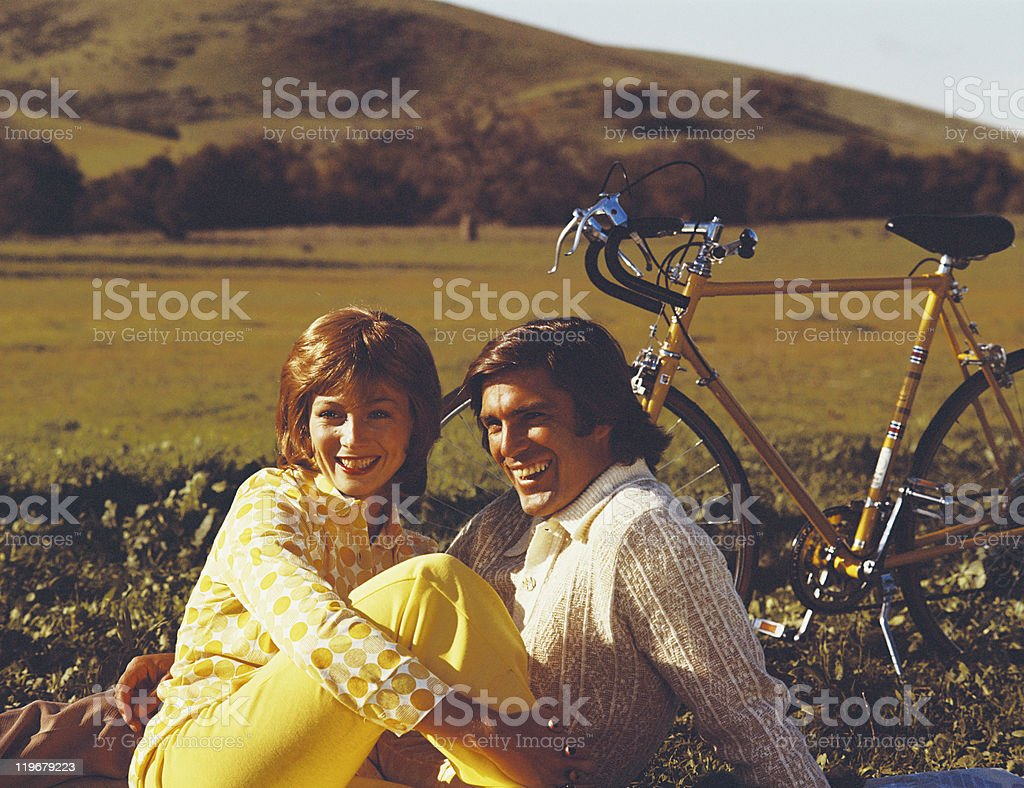 Couple sitting in field with bicycle, smiling stock photo