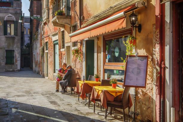 paar sitzt vor einem cafe in venedig, italien - italienischer abstammung stock-fotos und bilder