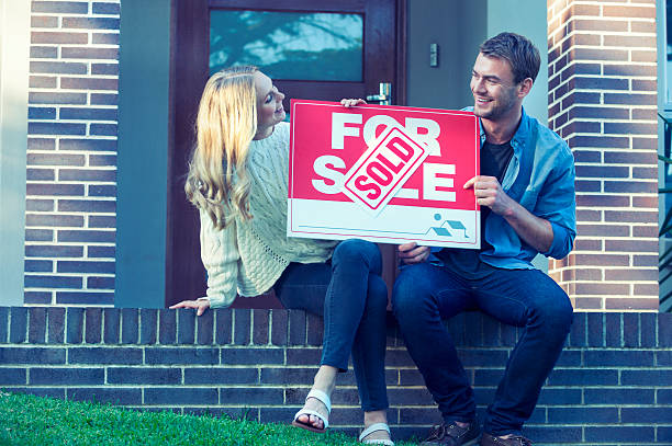 Couple sitting in front of a new home. stock photo