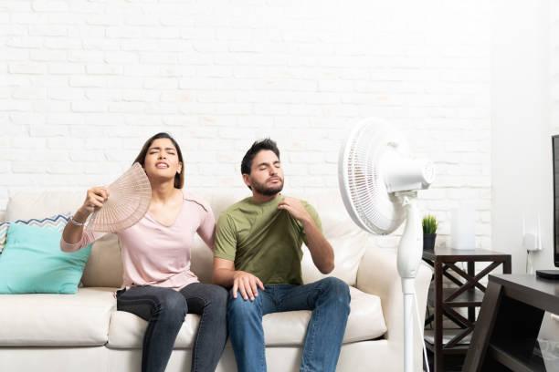 par sitter framför fläkten under varmt väder - kvinna ventilationssystem bildbanksfoton och bilder