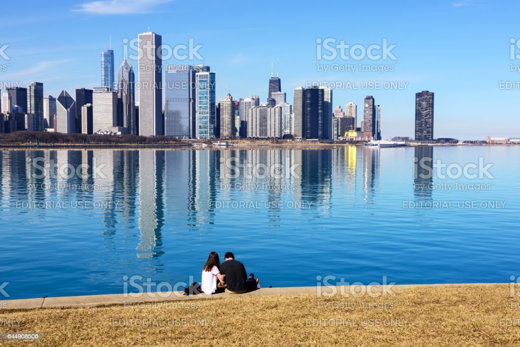 Couple sitting in front of Lake Michigan, Chicago skyline stock photo