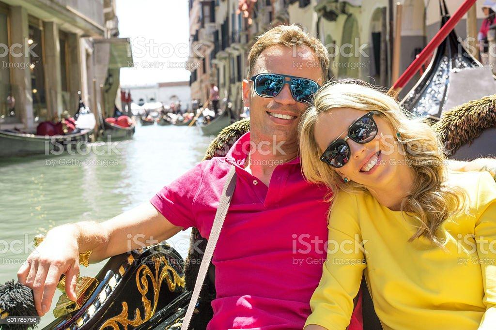 Couple sitting in gondola and smiling stock photo