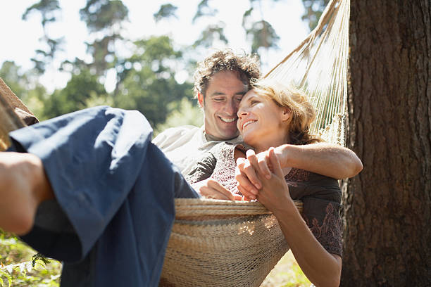 couple sitting in hammock - hangmat stockfoto's en -beelden