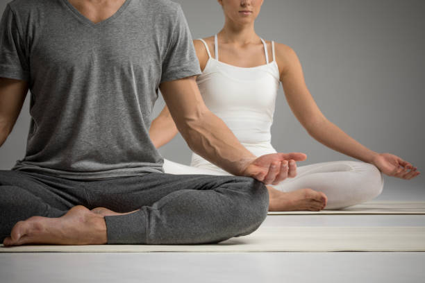 Couple sitting in lotus position stock photo