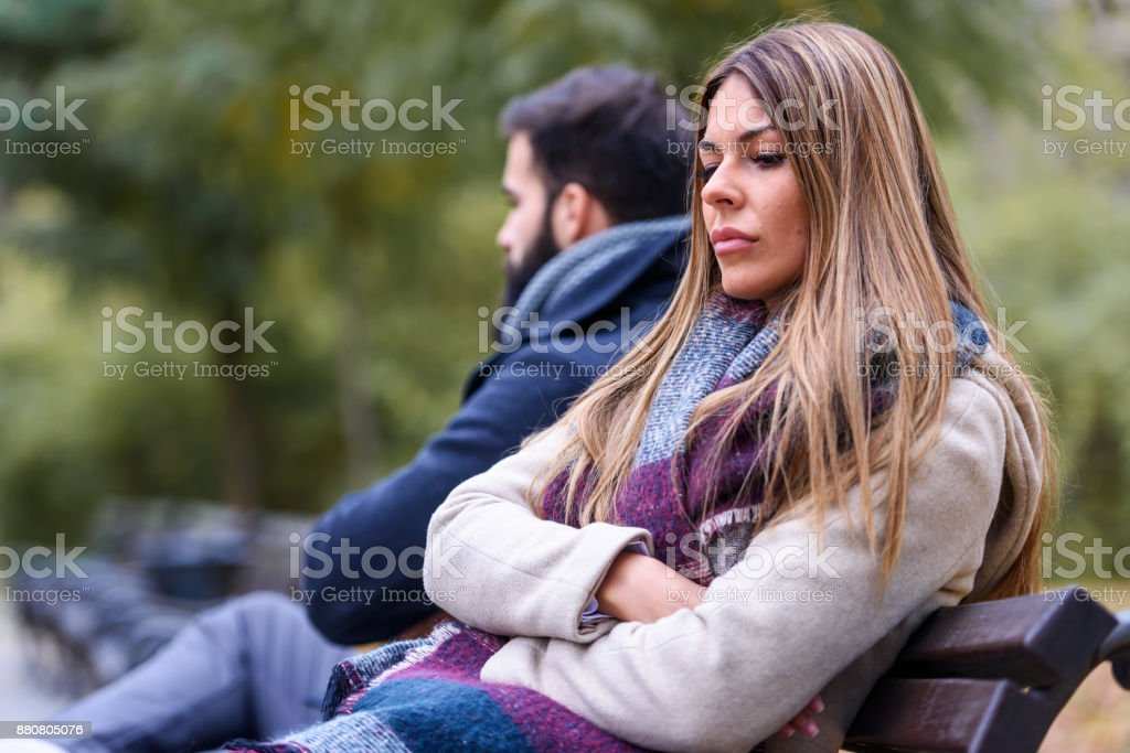 Couple sitting in park having relationship problems stock photo