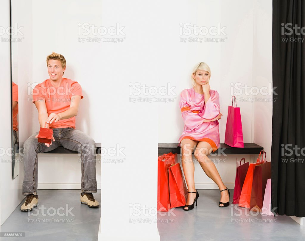 Couple sitting in shop's fitting room stock photo