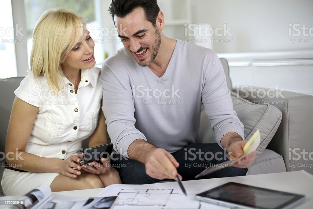 Couple sitting in sofa working on plans of future house royalty-free stock photo