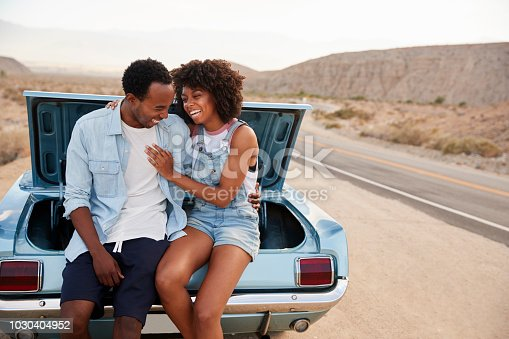 1030408008istockphoto Couple Sitting In Trunk Of Classic Car On Road Trip 1030404952