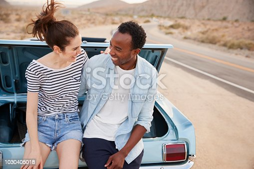 1030408008istockphoto Couple Sitting In Trunk Of Classic Car On Road Trip 1030405018