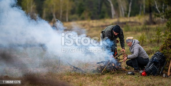 Mature couple sitting near camping fire in forest.