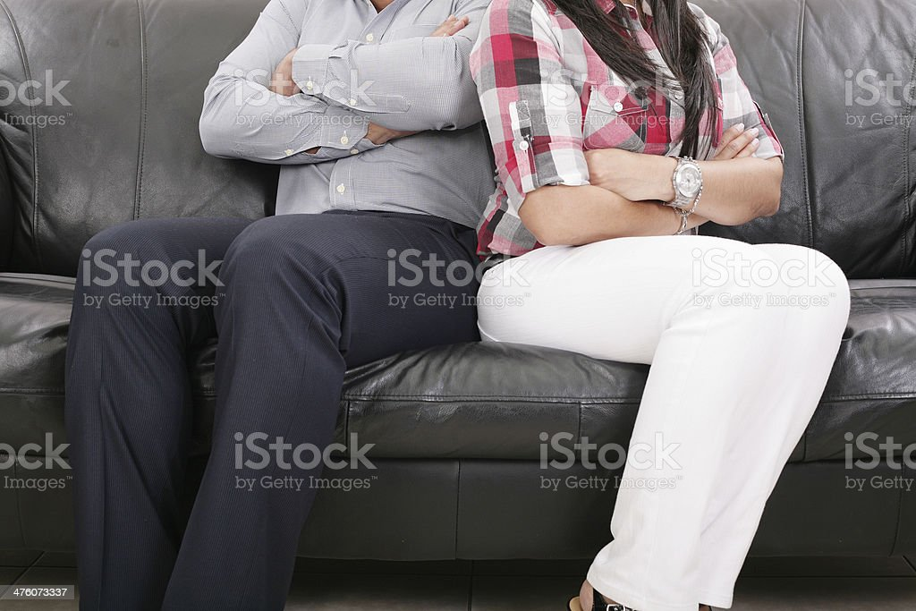 Couple sitting of the couch having problems stock photo