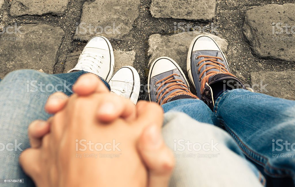 Couple sitting on a bench holding hands stock photo