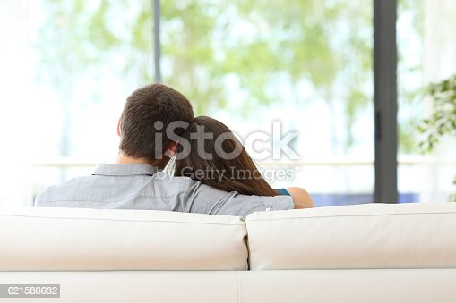 istock Couple sitting on a couch looking through window 621586682