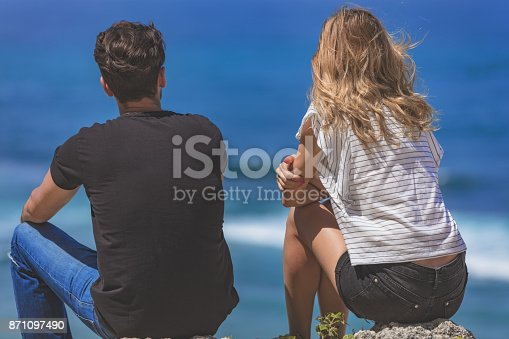 139880782istockphoto Couple sitting on a high cliff and looking at the sea / ocean. 871097490