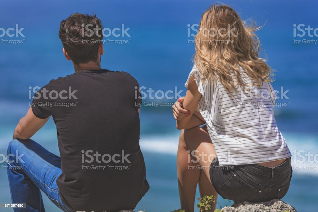 Couple sitting on a high cliff and looking at the sea / ocean. stock photo