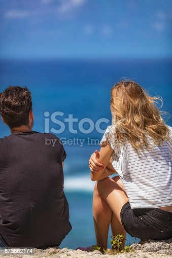 139880782istockphoto Couple sitting on a high cliff and looking at the sea / ocean. 873862174