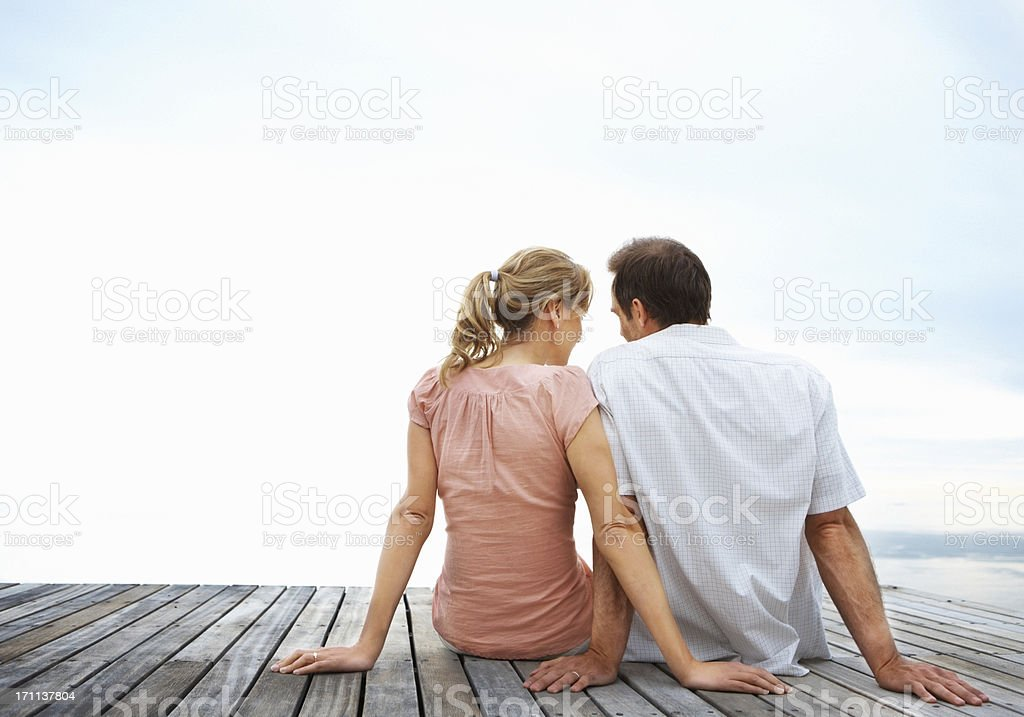 Couple sitting on a jetty royalty-free stock photo