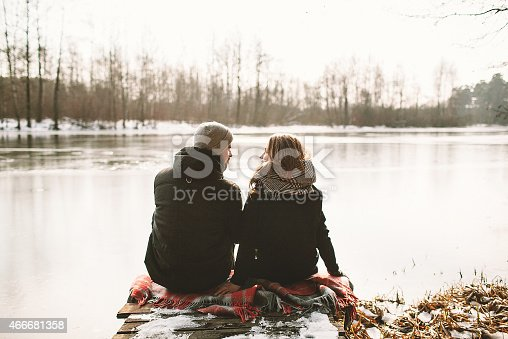 Young couple sitting on pier at frozen lake looking at each other in love, back view