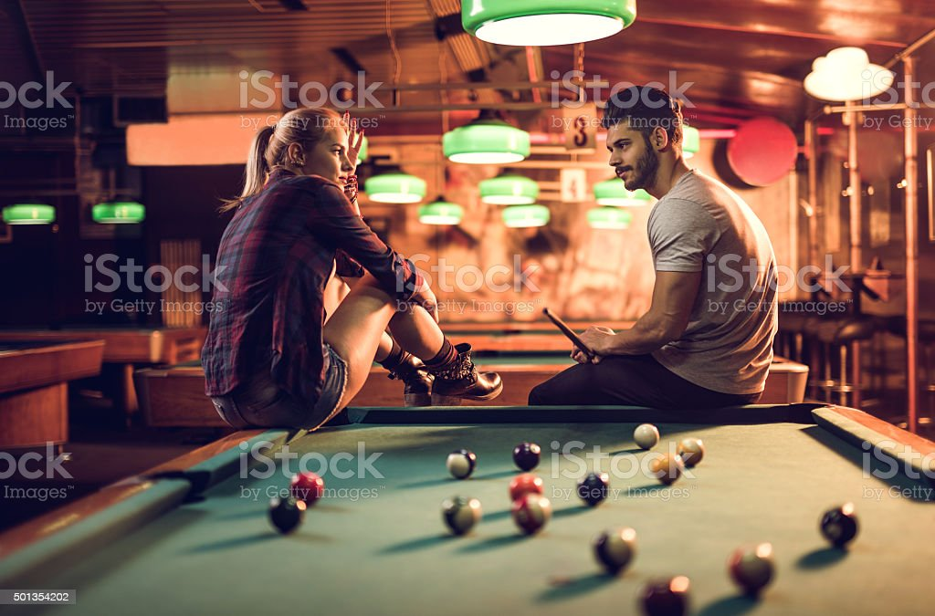 Couple sitting on a pool table in pub and talking. stock photo