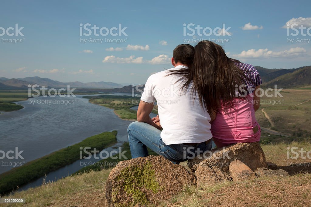 couple sitting on a rock in mountains royalty-free stock photo